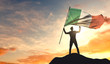 Ireland flag being waved by a man celebrating success at the top of a mountain. 3D Rendering