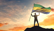 Gabon flag being waved by a man celebrating success at the top of a mountain. 3D Rendering