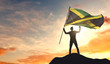 Jamaica flag being waved by a man celebrating success at the top of a mountain. 3D Rendering