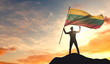 Lithuania flag being waved by a man celebrating success at the top of a mountain. 3D Rendering