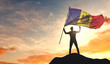 Moldova flag being waved by a man celebrating success at the top of a mountain. 3D Rendering