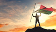 Madagascar flag being waved by a man celebrating success at the top of a mountain. 3D Rendering