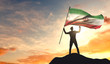 Iran flag being waved by a man celebrating success at the top of a mountain. 3D Rendering