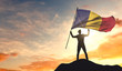 Romania flag being waved by a man celebrating success at the top of a mountain. 3D Rendering