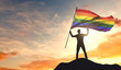 Gay pride flag being waved by a man celebrating success at the top of a mountain. 3D Rendering