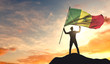 Senegal flag being waved by a man celebrating success at the top of a mountain. 3D Rendering