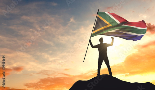 canvas print motiv - ink drop : South Africa flag being waved by a man celebrating success at the top of a mountain. 3D Rendering