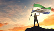 Sierra Leone flag being waved by a man celebrating success at the top of a mountain. 3D Rendering