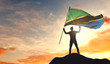 Tanzania flag being waved by a man celebrating success at the top of a mountain. 3D Rendering