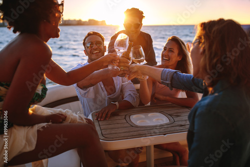 Fotografia  Group of friends having drinks at sunset boat party