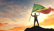 Republic of Congo flag being waved by a man celebrating success at the top of a mountain. 3D Rendering