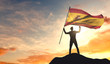 Spain flag being waved by a man celebrating success at the top of a mountain. 3D Rendering