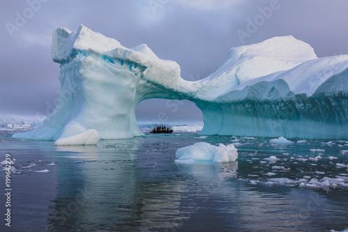 Deurstickers Antarctica A zodiac full of tourist viewed through an arch in a large iceberg, Antarctica