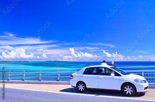 真夏の宮古島、伊良部大橋の駐車スペースから海を眺める観光客