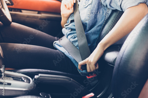 Asian woman fastening seat belt in the car, safety concept Fotobehang