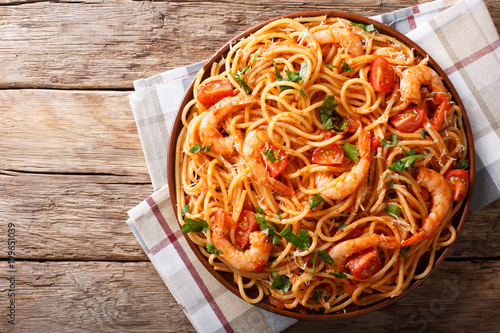 Spicy spaghetti with shrimps in tomato sauce close-up. Horizontal top view from above
