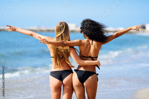 Rear view of two young women with beautiful bodies in bikini Poster