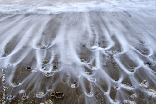 Photographie  Long exposed wave reaching shore.