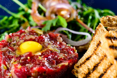 Dish with beef tartare, tomatoes and leaves in a cafe, close-up