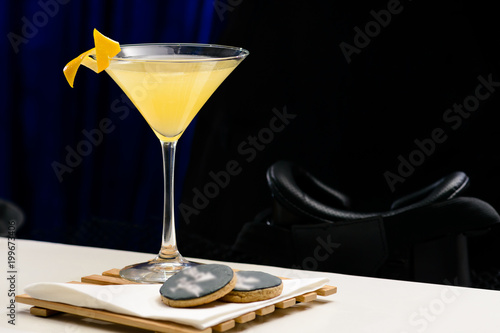 Fotomural  Citrus cocktail in a martini glass on dark background, shallow dof