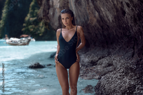 Beautiful girl in a black swimsuit enjoys a vacation on the islands