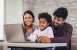canvas print picture - Girl and mixed race parents use laptop at home
