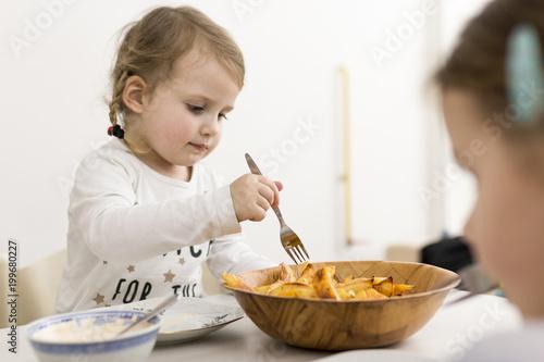 Foto op Canvas Kruidenierswinkel Little Girl Picking Fried Potato Wedges Up with Fork From Bowl