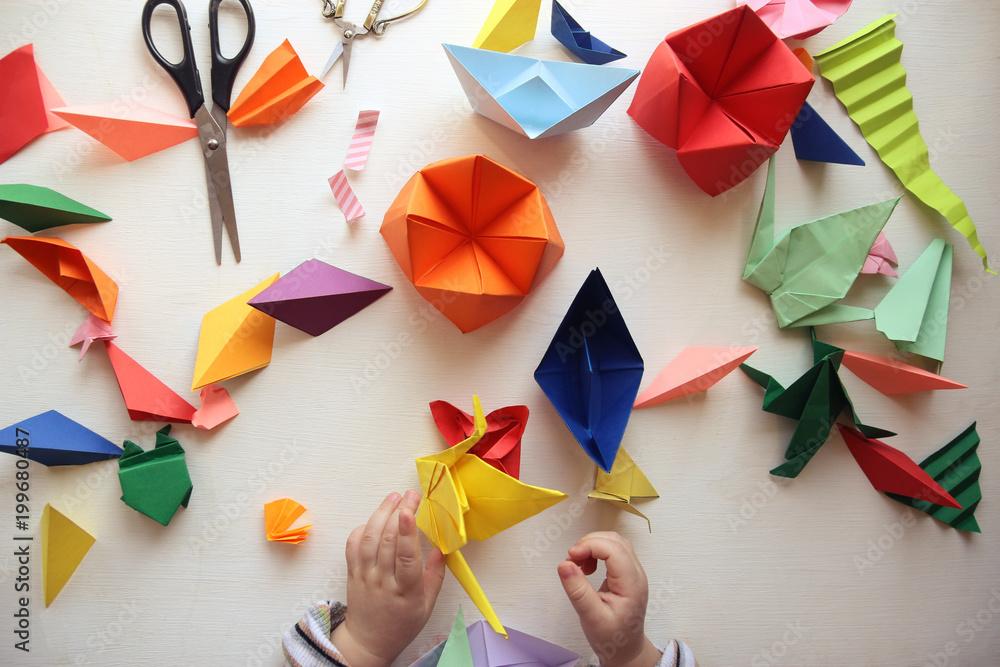 Fototapeta the child makes origami. Multicolored Origami and paper on  a white table. origami lesson