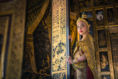 Valokuva Beautiful asia woman in gorgeous antique thai dress stand near ancient gold threads old thai pattern windows in temple of  Thailand