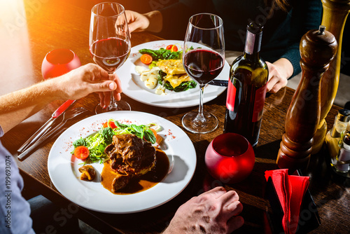 Spoed Foto op Canvas Restaurant Couple having romantic dinner in a restaurant in rays of the sun