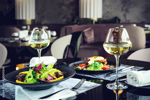 Romantic dinner at a restaurant. Appetizing dishes with meat and lettuce leaves and glasses with wine