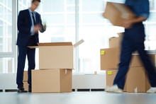 Businessman Standing Over Open Box By Window Of Office Center While Relocation Service Worker Carrying Packages