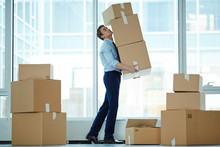 Young Businessman Carrying Huge Stack Of Big Boxes With Office Supplies During Relocation To Modern Business Center