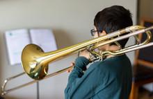 Menino A Tocar Trombone Em Casa.