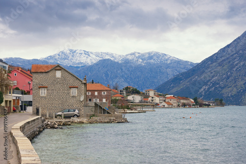 Poster Donkergrijs Small Mediterranean town near snow-capped mountains on cloudy day. Montenegro, Bay of Kotor (Adriatic Sea), Prcanj
