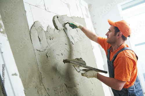 Fotografie, Obraz  Plasterer putting plaster on wall. slow motion