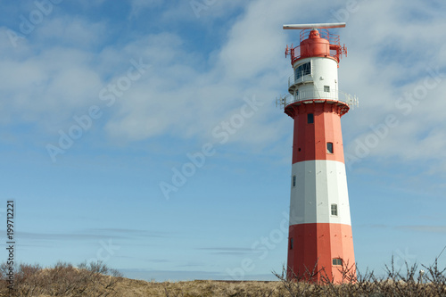 Foto op Aluminium Vuurtoren beautiful red and white lighthouse in nordic dune landscape