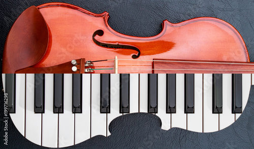 Photo  piano keys in to the violin on the black leather table, half keyboard like violi