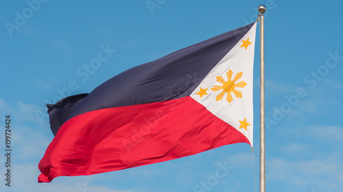 Fényképezés  Flying bicolor flag of the Philippines with central golden sun representing the provinces and stars the islands