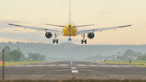 Fotografering  Landing aircraft at the airport of the city of Legazpi early in the morning
