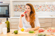 Pregnant woman preparing meal, vegetables, and eating pepper