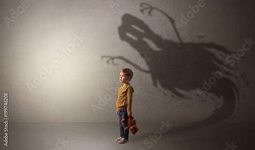Valokuva  Scary ghost shadow in a dark empty room with a cute blond child