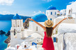 Leinwandbild Motiv Europe travel happy vacation woman. Girl tourist having fun with open arms in freedom in Santorini cruise holiday, summer european destination. Red dress and hat person.