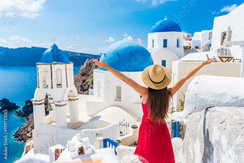 Obraz Europe travel happy vacation woman. Girl tourist having fun with open arms in freedom in Santorini cruise holiday, summer european destination. Red dress and hat person. - fototapety do salonu