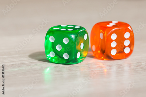 Colourful green and orange gambling dice on table плакат