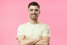 Portrait Of Smiling Handsome Man In Beige Tshirt And Trendy Transparent Eyeglasses Standing With Crossed Arms Isolated On Pink Background