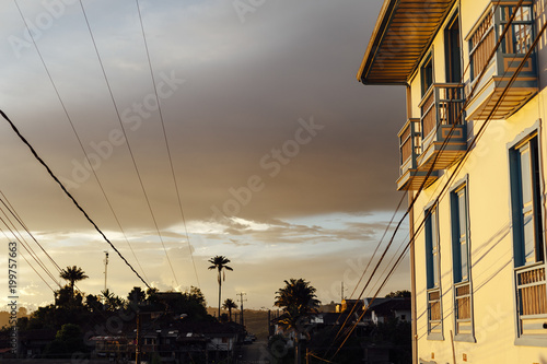 Sunset, palm trees and colonial balconies with shadows and white wall in Salento, Colombia
