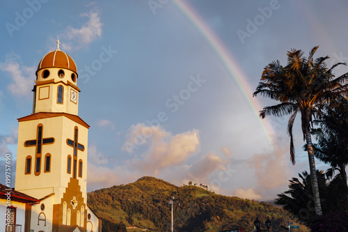 Salento church bell tower under a rainbow on a stormy afternoon, Quindio, Colombia