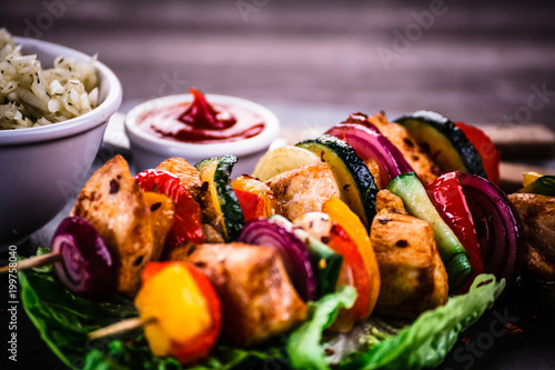 Kebabs - grilled meat with vegetables on wooden background
