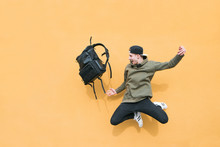Street Young Man Jumping With A Backpack On The Background Of An Orange Wall